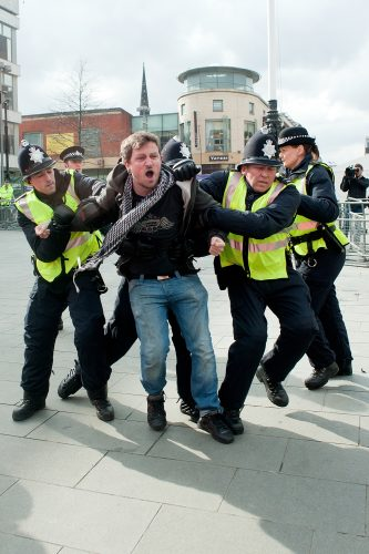 Protestor is grabbed by police after crossing the