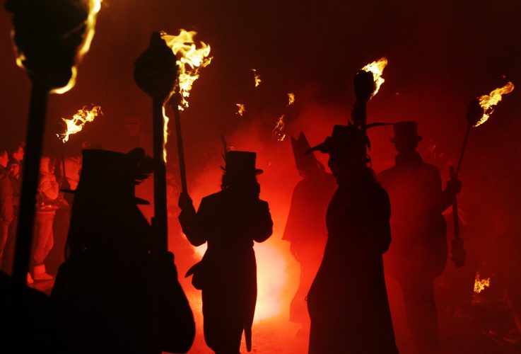 Participants parade through the streets carrying flaming torches during the Bonfire Night processions in Lewes, England