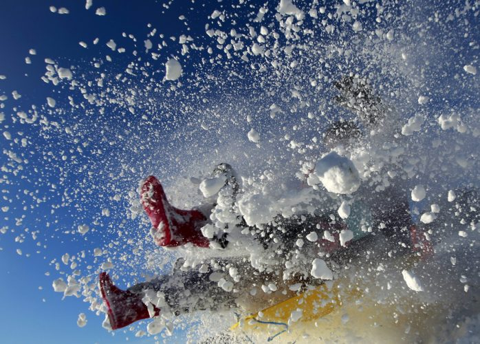 A sledger's boots are visible in an explosion of snow during an attempt to jump a ramp at the Queen Elizabeth country park