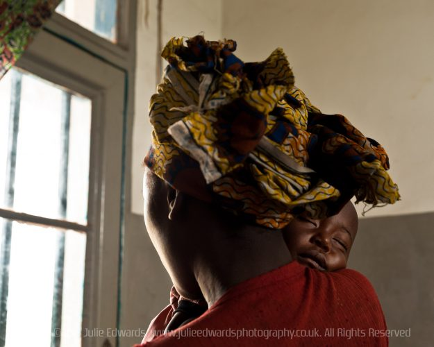 A war rape victim hides her face whilst holding her baby at the Centre de Sante de Kanyaruchinya. Rape is common in the Democratic Republic of Congo.