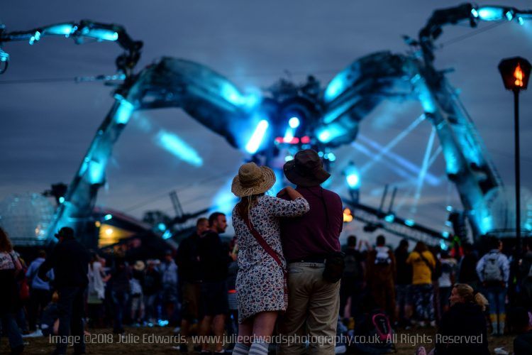 A couple watch the Arcadia lightshow at Glastonbury Festival 2015