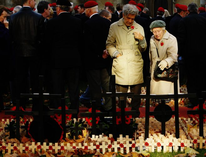 A couple pause among crosses and poppies in the Field of Remembrance in the grounds of Westminster Abbey in London