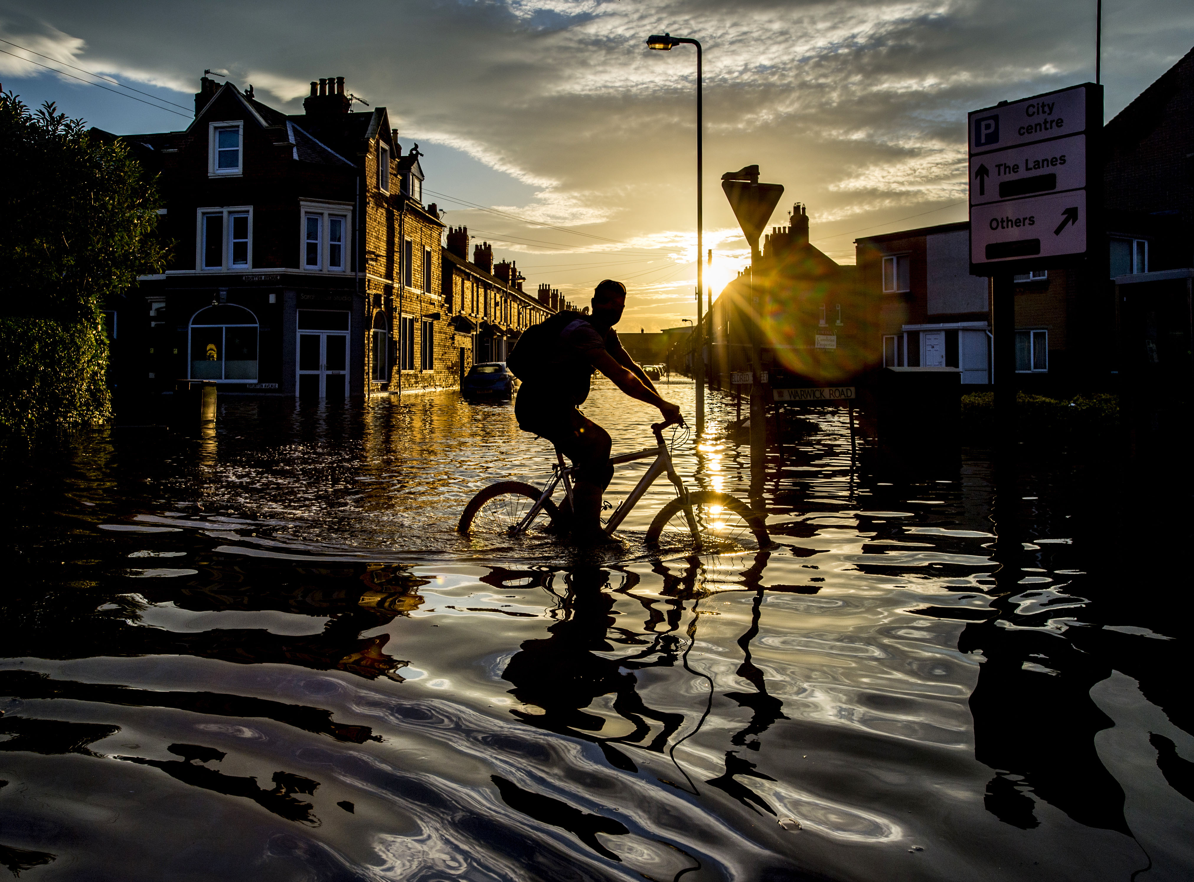 Bruce Adams - A cyclist travels through flood water along Warwick Road, Carlisle, after severe flooding across the county. December 7, 2015