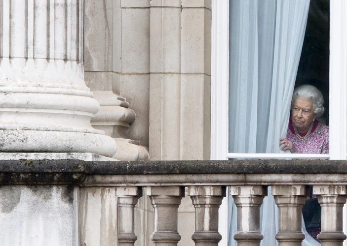 Queen Elizabeth II peers through the curtains of Buckingham Palace as she waits for The Patrons Lunch to start on The Mall12 Jun 2016
