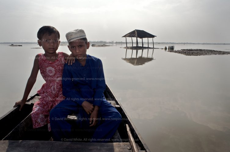 Children who had seen their homes washed away float out on a boat to show the photographer where their homes once stood, central Bangladesh. Illustrating climate change in Bangladesh. For DFID.