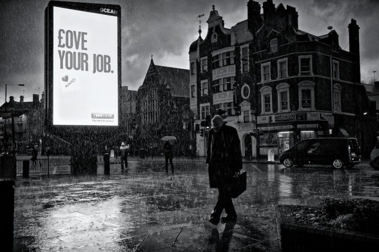 A heavy downpour of rain soaks pedestrians as they pass an illuminated advertising sign saying