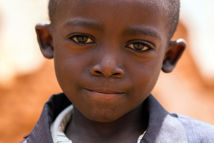 A young boy waits patiently outside a church after Sunday service, in the rural village of Chimlata, in central Tanzania.
