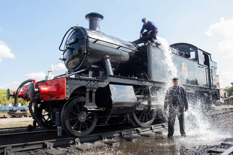 On a hot July day, during a heatwave, steam train driver Andy Christie gives fireman Gary Williams a refreshing shower from the water pump, at Severn Valley Railway, Kidderminister, Worcestershire.