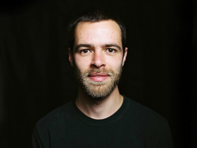 Musician Aron Kyne sits for a portrait.