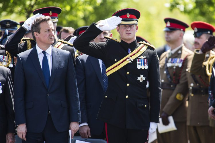 Prince Harry salutes watched by Prime Minister David Cameron