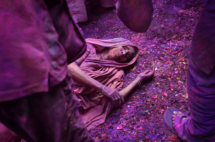 Vrindavan, Uttar Pradesh, 3rd March 2015.  An Indian widow lies on a patio floor covered in flower petals and colored powder as she celebrates Holi or 'festival of colors' at the Meera Sahabhagini Mahila Ashray Sadam widows Ashram in Vrindavan, Uttar Pradesh, March 3rd 2015.  The widows of this and other ashrams in this northern town are sponsored by the NGO, Sulabh International which funds most of their needs. Shunned from society when their husbands die, not for religious reasons, but because of tradition, many Indian widows have been ostracised from society and no longer live with their families and are forced to beg for food. Almost 2,000 of the estimated 34 million widows currently living in India live in Vrindavan and benefit from the welfare extended by the NGO.