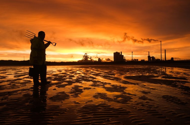 A man digs for fishing bait on the beach at low tide at South Gare on Teesside.