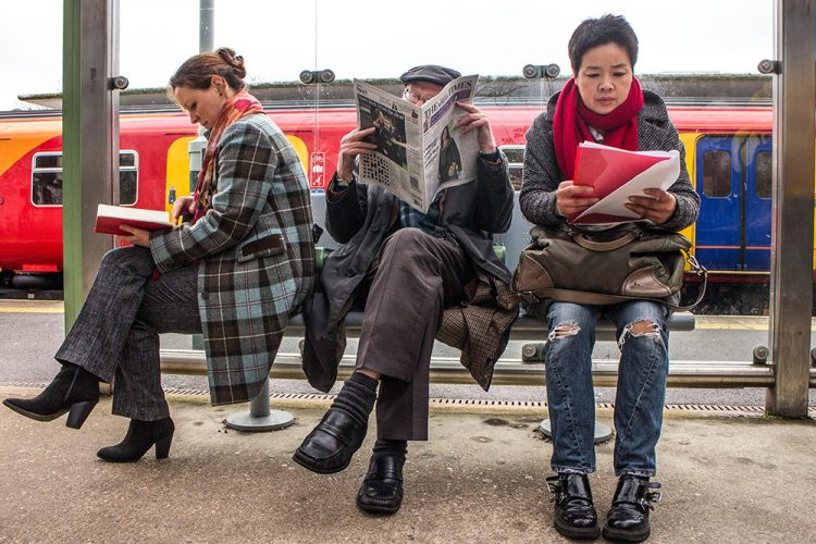 Three Strangers Sitting On A Railway Station Bench Reading A Boo