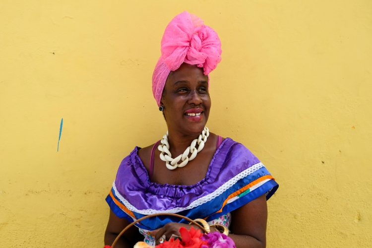 A woman wearing a colourful and traditional outfit sits on the side of a street in Habana Vieja in Cuba.