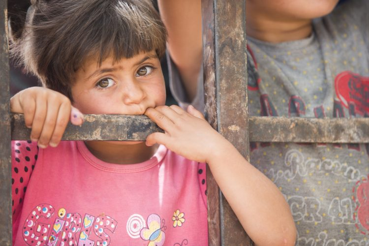 A girl looks out through the fence at a Nizip refugee camp, Turkey on the Northern Syrian border.  This packed refuge, funded by the EU, has been closed for more than five years to new refugees meaning that children of this age have only ever known camp life.