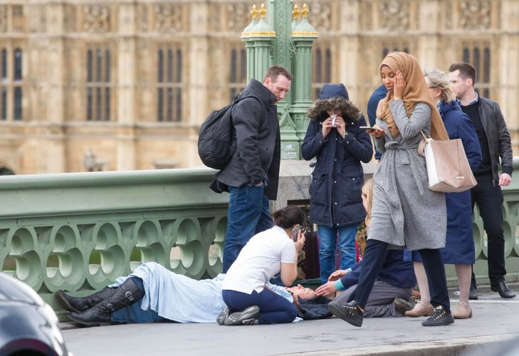 Passers-by treat a victim after 52-year-old Briton Khalid Masood drove a car into pedestrians along the south side of Westminster Bridge injuring more than 50 people.