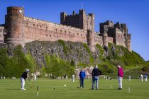BAMBURGH, UK. Members of Bamburgh Croquet Club enjoy a game below the imposing Bamburgh Castle and crystal blue skies with the village's cricket team also playing in their final game of the season against the Nairobi Nomads. Photo © Matthew Lofthouse/North News & Pictures Ltd. 07712784320. Dated: 06/09/2020.