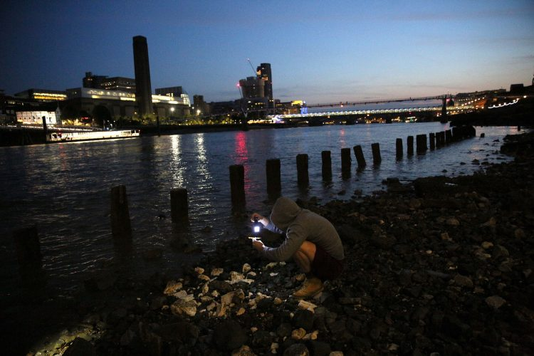 A mudlarker uses a torch to look for items on the bank of the river Thames in London