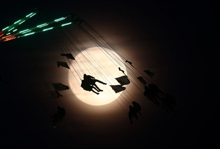 People on a funfair ride are seen against the moon a day before the