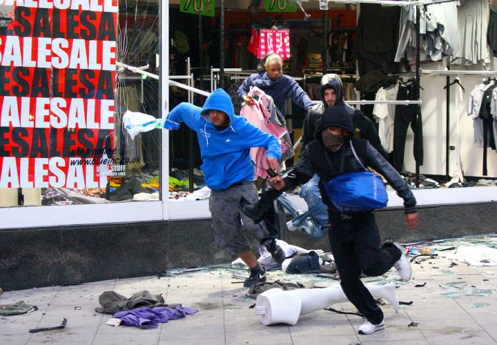 Rioters jump out of a shop in Peckham after looting its contents