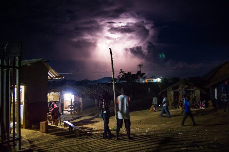 Men watch a thunderstorm, eastern Congo