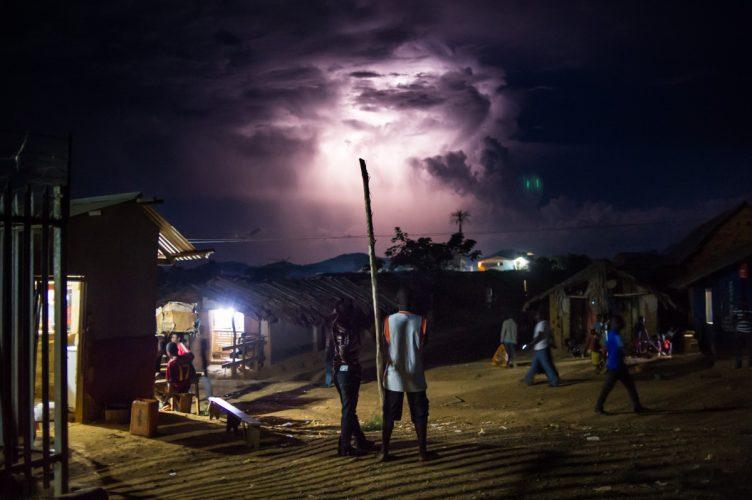 Men watch a thunderstorm, eastern Congo