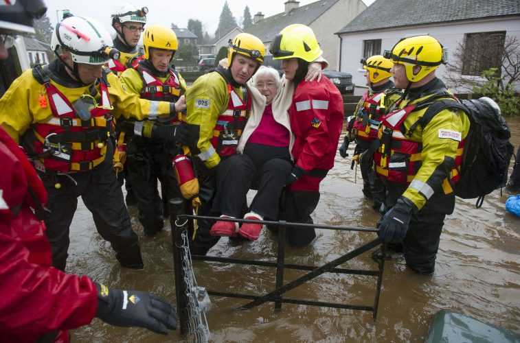 Firefighters carry a pensioner to safety after her house in the village of Comrie was flooded.