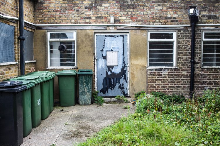 Derelict Unused Brick Building With a Line of Council Wheely Bin
