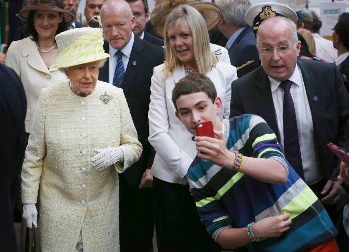 A local youth takes a selfie photograph in front of Queen Elizabeth II during a visit to St George's indoor market on June 24, 2014 in Belfast, Northern Ireland