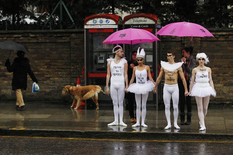 Human rights campainers' ballet dancers wait to cross a road to protest outside the Russian Embassy in London.