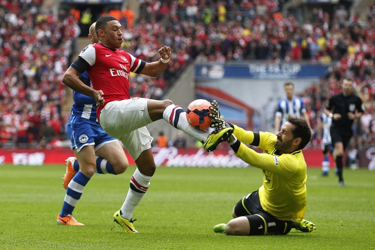 Wigan Athletic's goalkeeper Scott Carson, right, stops a shot from Arsenal's Alex Oxlade-Chamberlain during their English FA Cup semifinal soccer match at Wembley Stadium in London.