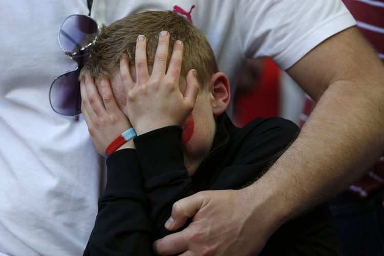 A young Sheffield United's supporter cries over the lost of his team to Hull City at the end of their English FA Cup semifinal soccer match at Wembley Stadium in London.
