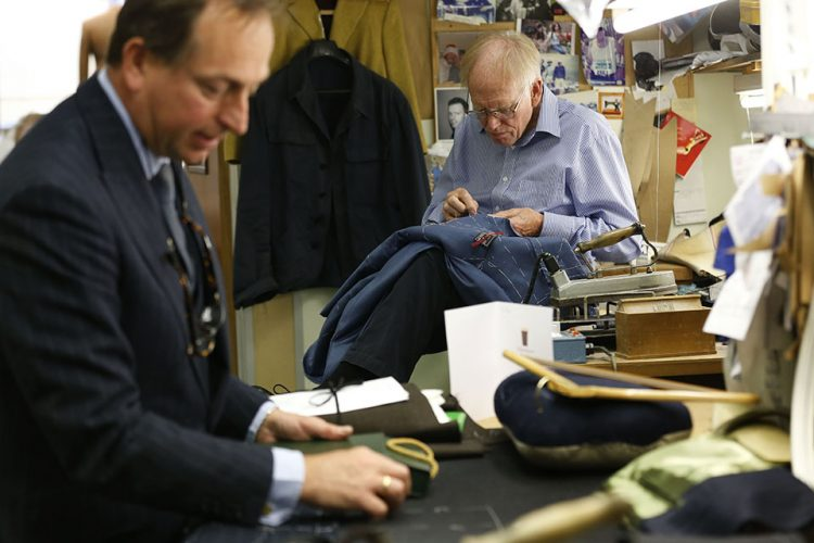 A tailor, right, works on a suit as Simon Cundey, managing director of Henry Poole & Co tailor speaks to reporter at his store on Savile Row in London.
