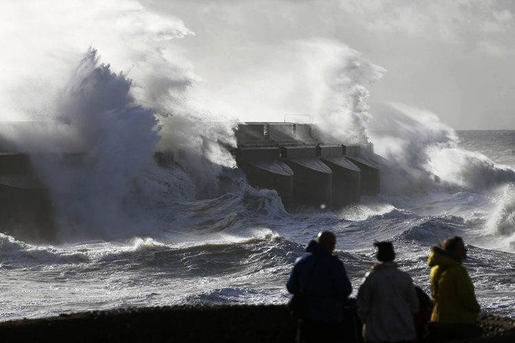 People watch the waves batter into the wall of a marina in Brighton, England.