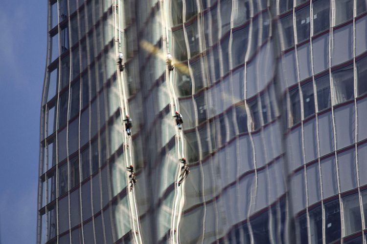 Reflected in a nearby building, Greenpeace protesters climb up The Shard i, the tallest building in western Europe, in London during a protest against the oil company Shell's drilling in the Arctic.