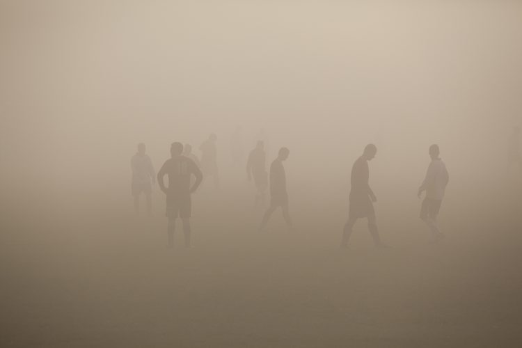 Sunday footballers play through fog in North London. Highgate Woods.