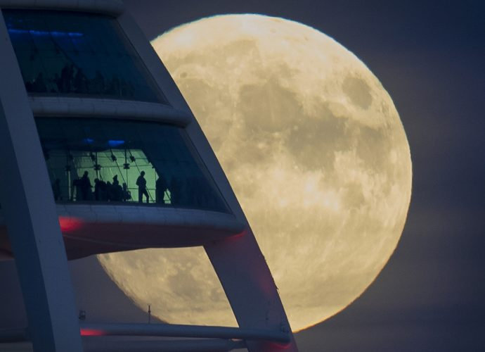 People in the Spinnaker Tower in Portsmouth get a clear view of the near full super moon as it rises. November 13, 2016.