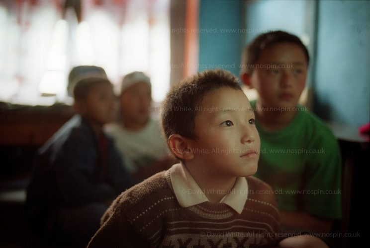 Bhutan and the arrival of television. Bhutan was the last country in the world to accept television. Here, four young schoolboys watch American cartoons on a Murdoch satellite channel. they should be doing their homework. Essay for the Guardian magazine.
