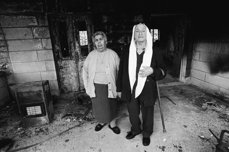 An elderly Palestinian Christain couple stand in the remains of their house after being shelled by the Israeli Army. Beit Sahour, Occupied Palestine...