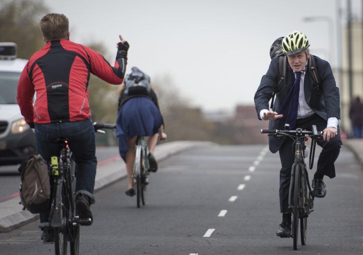 Vauxhall Bridge, London, UK. 19th November, 2015. Boris Johnson MP, is given the finger by a passing fellow cyclists as the Mayor officially launches the capital's first fully segregated cycle superhighway.