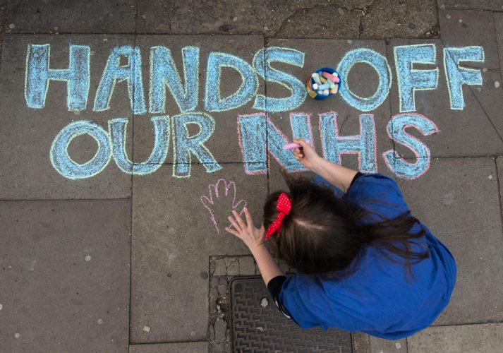 A junior doctor draws in chalk the pavement outside Kings Hospital during strike action
