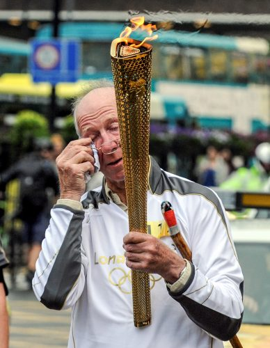 Football legend Jack Charlton, wipes a tear away during the Olympic torch relay in Newcastle