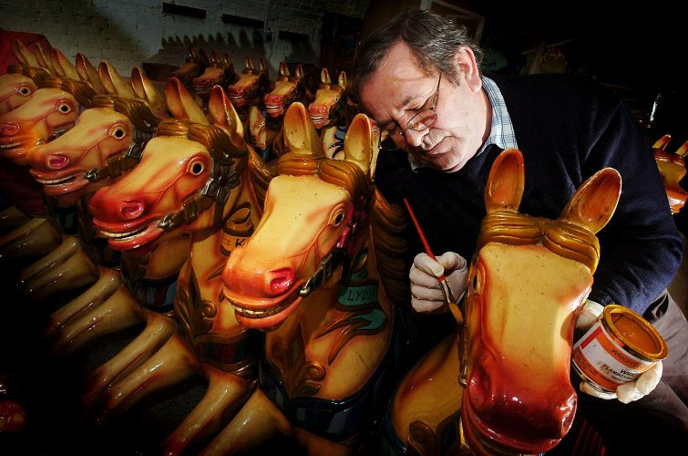 Carousel owner Owen Smith repainting the horses of the vintage ride on Brighton seafront © Terry Applin