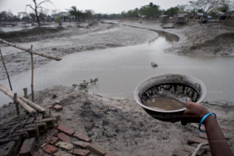 Climate change Bangladesh. A woman holds a food bowl whilst standing at the top of a dam that burst and flooded her village. Central Bangladesh. For DFID.
