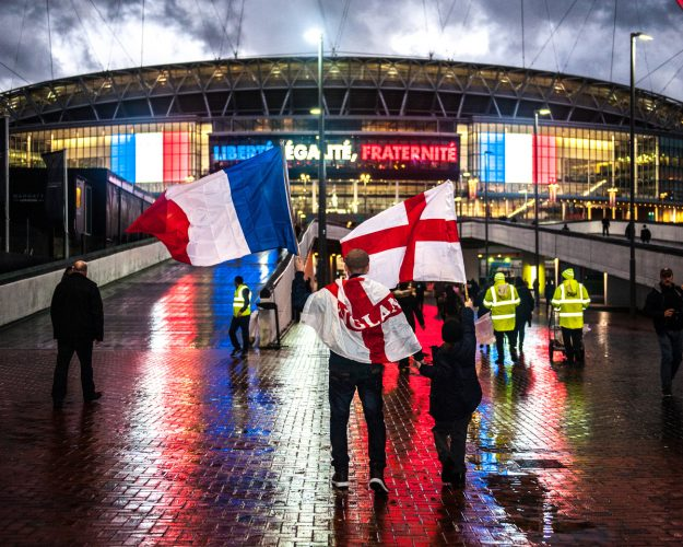 Fans waving English and French Tricolorè flags arrive at Wembley Stadium ahead of tonights match. The stadium is lit up with French Tricolour flags and the message 'Libertè, Ègalitè, Fraternitè' in memory of those killed in the recent terror attacks.