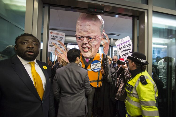 UNITED KINGDOM, London : A protest by lawyers against cuts to legal aid, along with a giant puppet of Justice Secretary Chris Grayling is prevented by police and security from entering the Ministry of Justice.