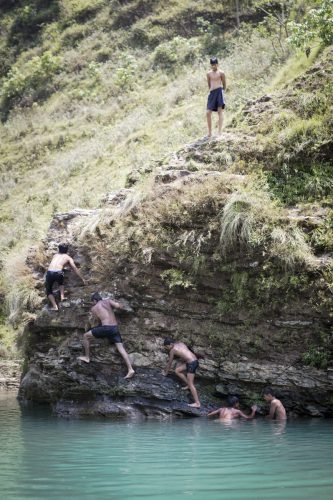 Nepal - young men climb a rock.