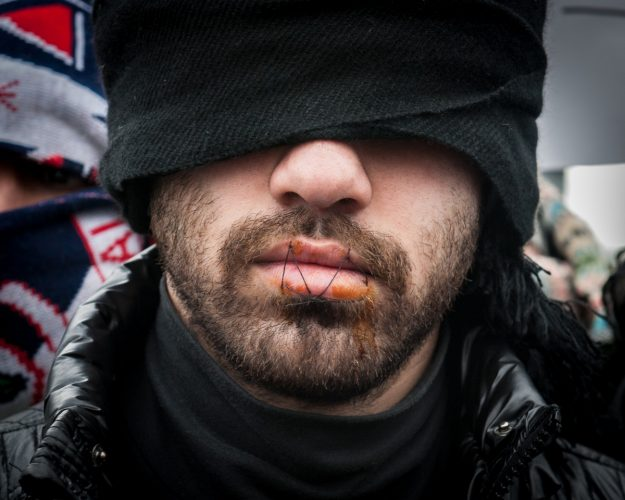 Refugees stich their mouths shut during protest at the Calais Jungle.