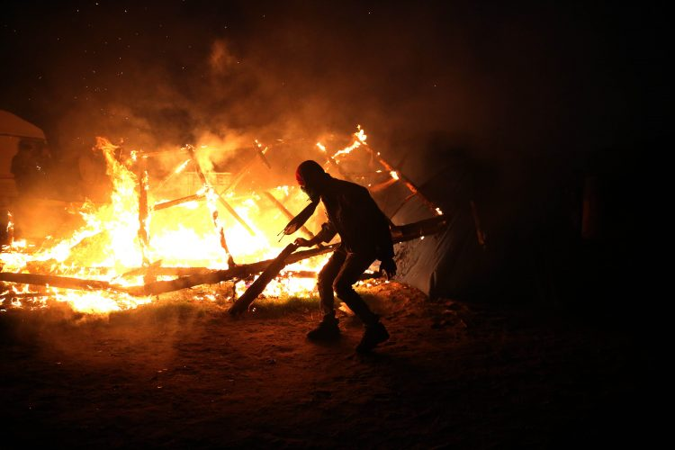A migrant burns his temporary shelter as the '