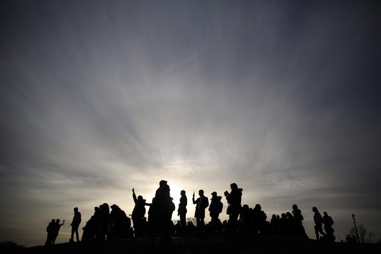 People are silhouetted as the sun sets on a winters afternoon in Primrose Hill in London